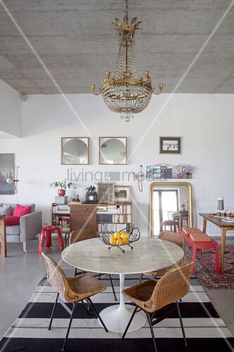 Runder Tisch mit Rattanstühlen unter Kronleuchter, im Hintergrund rote Bank, Goldrahmenspiegell und Bücherschrank