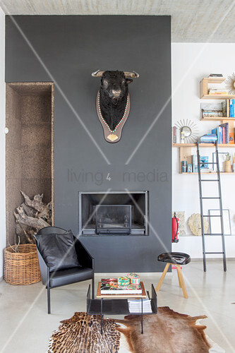Cowhide rug, side table and black chair in front of bull's head on black wall above fireplace