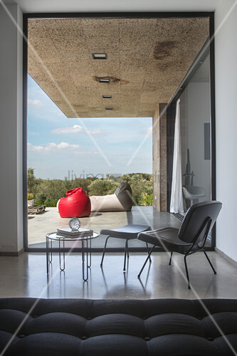 Elegant chair, footstool and side table in front of glass wall with view onto terrace