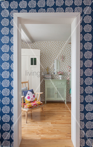 View through open door in wall with polka-dot wallpaper into bedroom