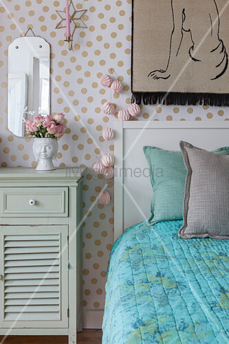 Mint-green bedside cabinet and bed against polka-dot wallpaper