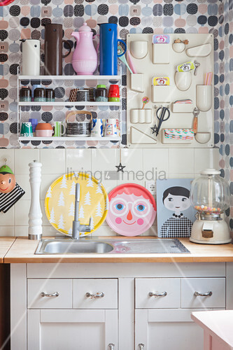 Colourful utensils in kitchen with polka-dot wallpaper