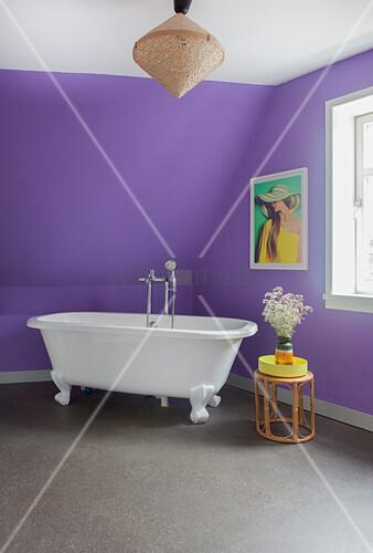 Free-standing bathtub below sloping ceiling in purple bathroom