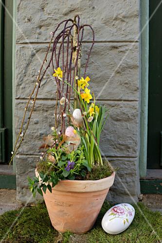 Palmkätzchen mit Ostereiern dekoriert, Narzissen und Moos im Pflanzentopf neben Dekoei am Hauseingang