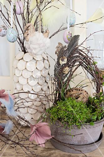 Birkenkranz mit Wachteleiern und Federn in Pflanzenschale, dahinter Zweige mit Ostereiern in Vase