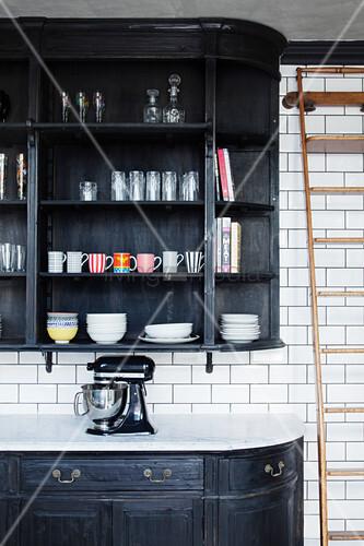 Black-painted dresser made from repurposed boikshelves on tiled wall