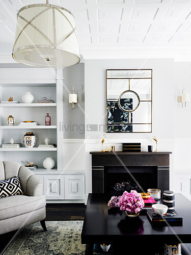 Helles Wohnzimmer mit dunklem Couchtisch, Kamin und Regal