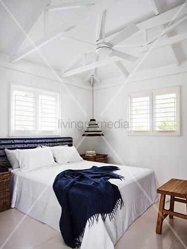 Doppelbett und Deckenventilator im Schlafzimmer mit weißem Dachkonstruktion aus Holz