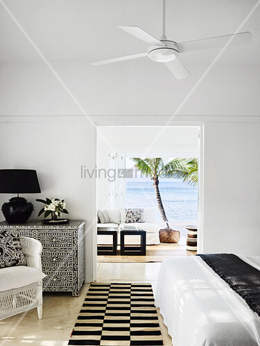 Blick auf Kommode mit Perlmutt- Intarsien im Schlafzimmer, im Hintergrund Wohnzimmer und Meerblick