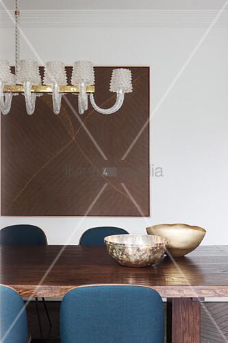 Goldene Schalen auf massivem Holztisch mit blauen Stühlen