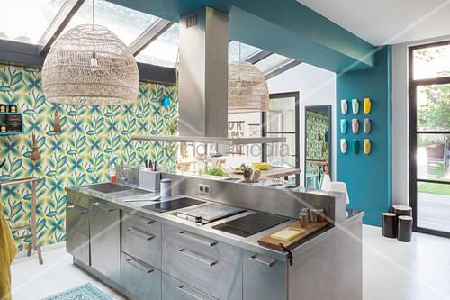 Edelstahl-Kochinsel in offener Küche, tapezierte Wand – Bild kaufen ...