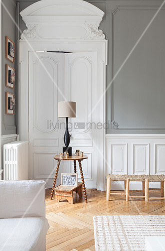 Table lamp on side table in front of elegant white double doors in renovated period apartment