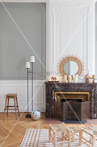 Hocker und Stehleuchte neben Kamin mit Marmorverkleidung in renovierter Altbauwohnung