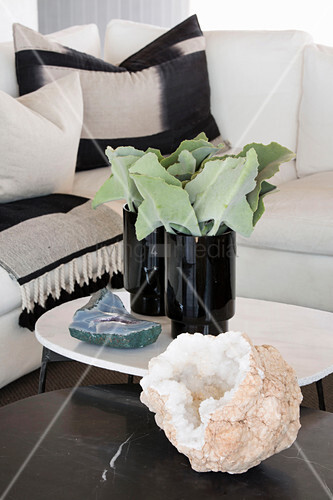 Stone encrusted with crystals and vases of leaves on coffee table