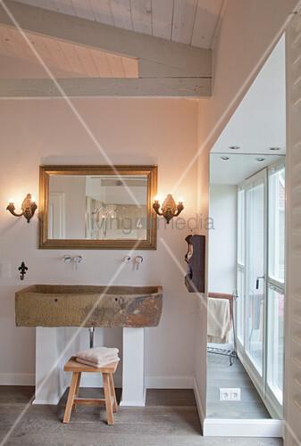 Rustic trough used as washstand in minimalist bathroom