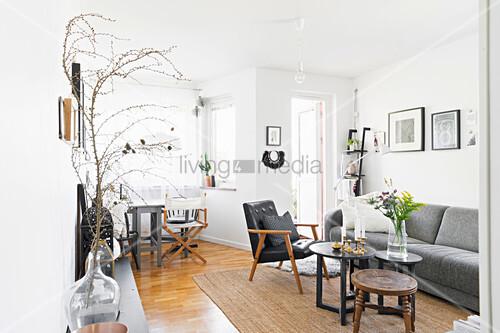 Graues Polstersofa, Lederstuhl und Coffeetable im Wohnzimmer mit weißer Wand