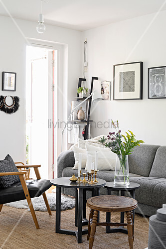 Coffee table, leather chair and grey sofa in living room with white walls