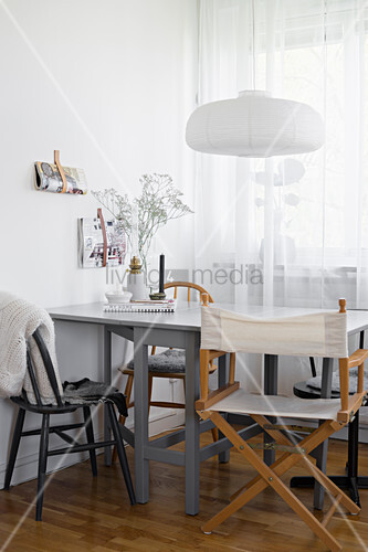 Grey dining table and various chairs next to window