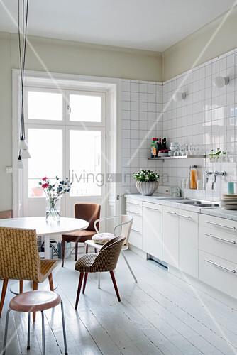 Verschiedene Retrostühle um runden Tisch vor weißer Küchenzeile