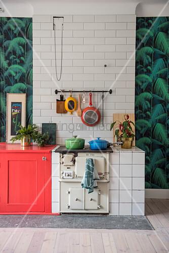 Alter Küchenofen an gefliester Wand zwischen Tapete mit Dschungelmotiv