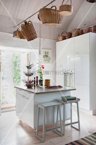 Stange mit Körben über der Kücheninsel mit zwei Barhockern