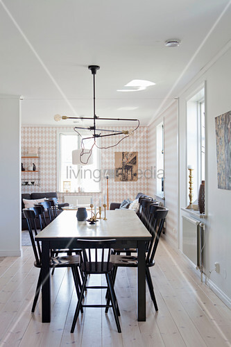 Black dining table and Windsor chairs in front of living room