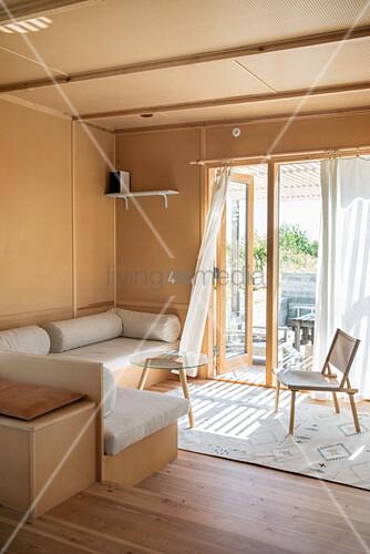 Sonnenlicht fällt durch offene Terrassentür ins Wohnzimmer