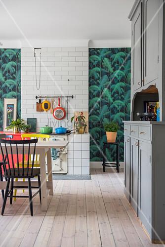 Bunte Farbakzente in der Küche mit Esstisch und altem Buffetschrank