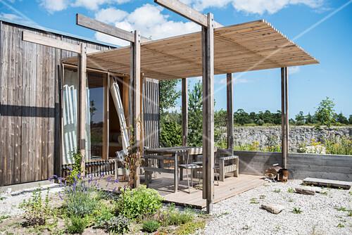 Überdachte Terrasse am schlichten Holzhaus bei blauem Himmel
