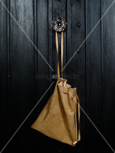 Pale leather bag hung from furniture door knob