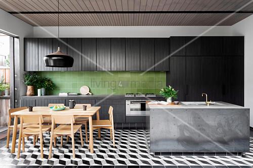 Schwarze Küchenzeile mit grünen Wandfliesen, Beton-Kücheninsel und Essbereich