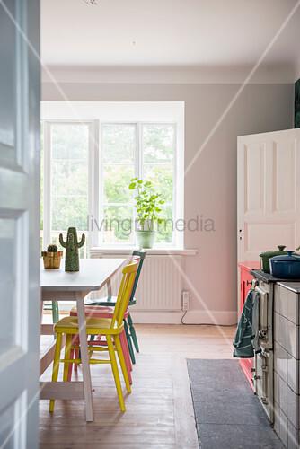 Blick in die Küche mit bunten Stühlen am Tisch vor dem Fenster