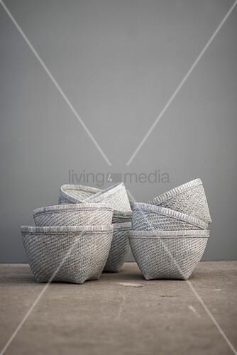 Gestapelte weiße Bastkörbe vor grauer Wand