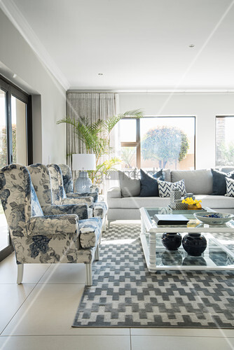 Restored wing-back chair, glass coffee table and sofa in bright living room with grey and white rug