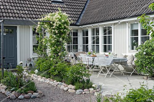 Hof mit Blumenbeeten und Terrasse vorm weißen Schwedenhaus
