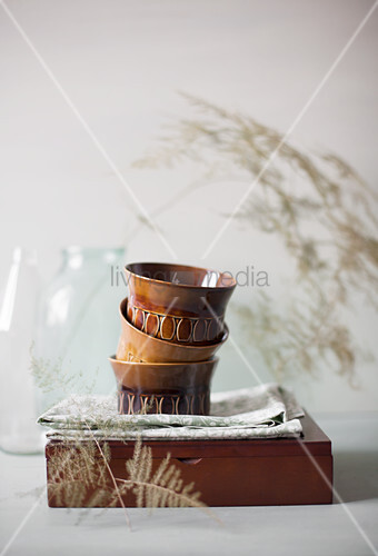 Stacked, brown, retro bowls on cloth and wooden box