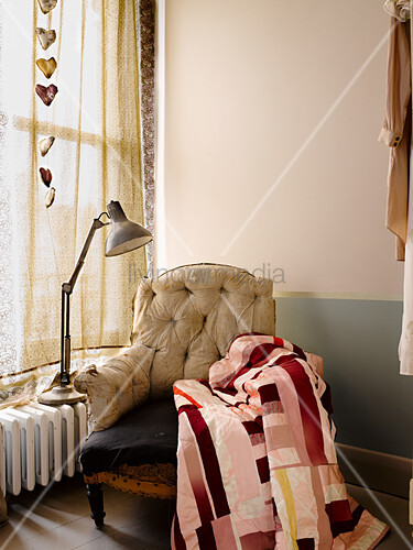 Patchworkdecke auf altem Sessel ohne Bezug vor dem Fenster