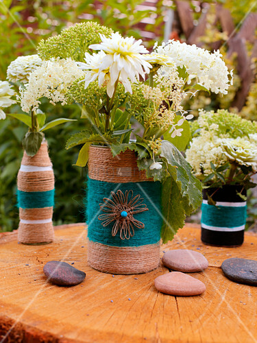 Bottle and tin can covered with cord and used as vases