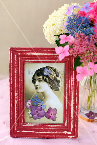 Vintage photo decorated with pressed flowers in red frame