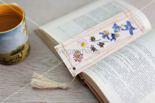 Lesezeichen mit gepressten Blumen, Fäden und einer Quaste