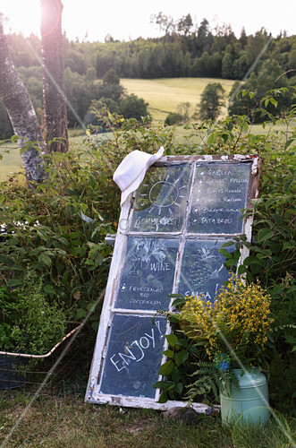 Menu written on old lattice window in garden