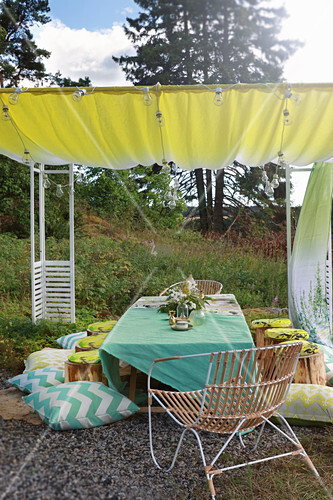 Set table with green tablecloth, chair, tree-stump stools and cushions under awning