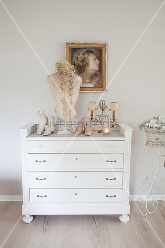 Vintage bust and old shoes on top of white chest of drawers