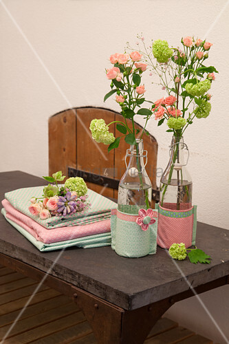 Flowers in swing-top bottles with fabric covers next to stacked folded fabrics