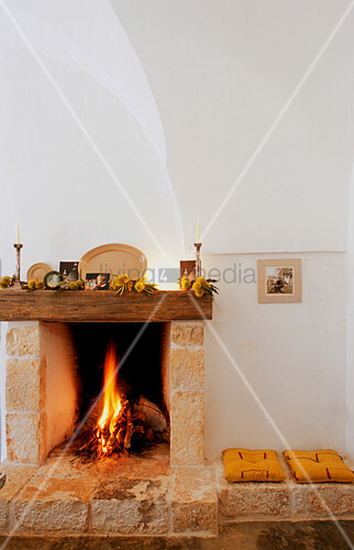 Fire in open stone fireplace with masonry bench on one side