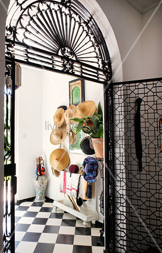 Collection of hats in hallway seen through open wrought iron door