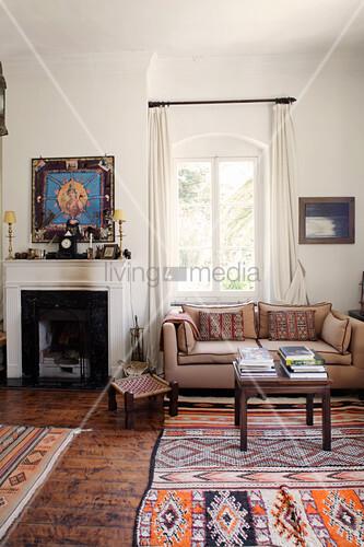 Couch neben Kamin im Wohnzimmer, gemusterter Teppich in Ethno-Look