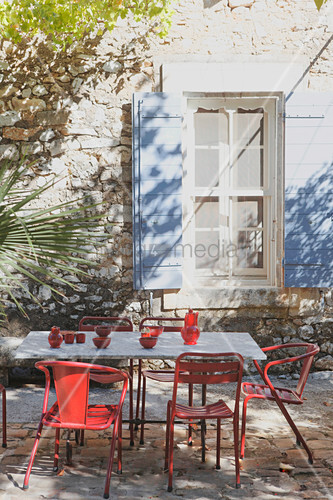 Table and vintage chairs on terrace outside Provençal house