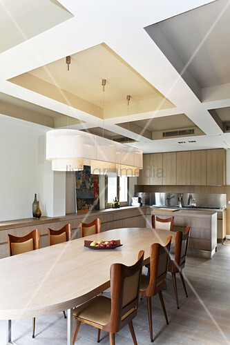Curved chairs at dining table below modern coffered ceiling