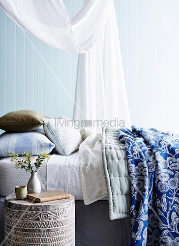 Bett mit Baldachin, Kissen und Decken, daneben Nachttisch aus Teakholz